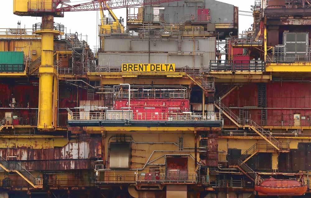 Een offshoreboorplatform van Shell wordt naar de haven gesleept om ontmanteld te worden. Shell investeert nog steeds miljoenen in de exploratie van nieuwe aardolievelden.  © Scott Heppell / AFP