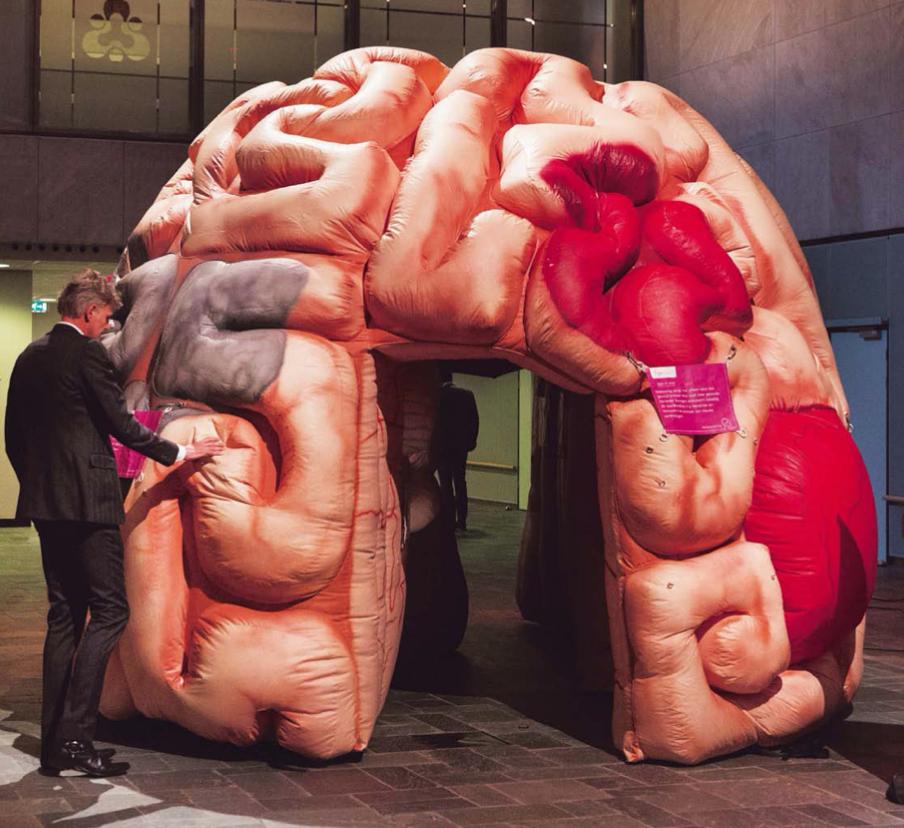 Een bezoeker van de Innovation for Health-conferentie, op 13 februari jl. in Rotterdam, bevoelt een opblaasbaar brein. Een belangrijk deel van het conferentieprogramma was gewijd aan dementie en alzheimer. – © Michel Porro / Getty