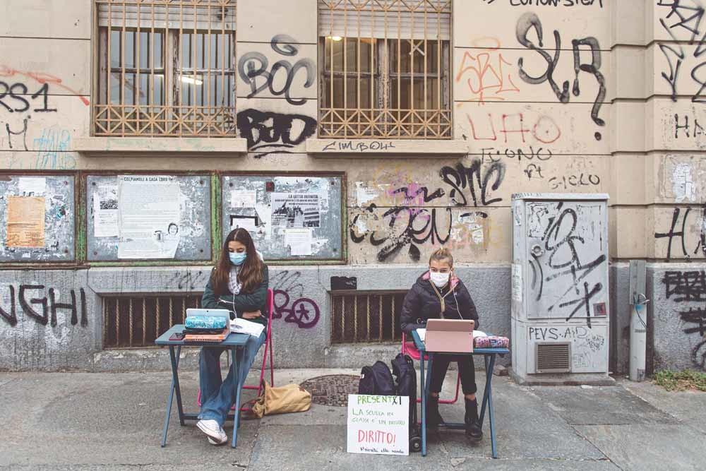 Twee leerlingen in Turijn volgen onlinelessen op de stoep van hun school uit protest tegen de lockdown in Italië. – © Nicolò Campo / Getty