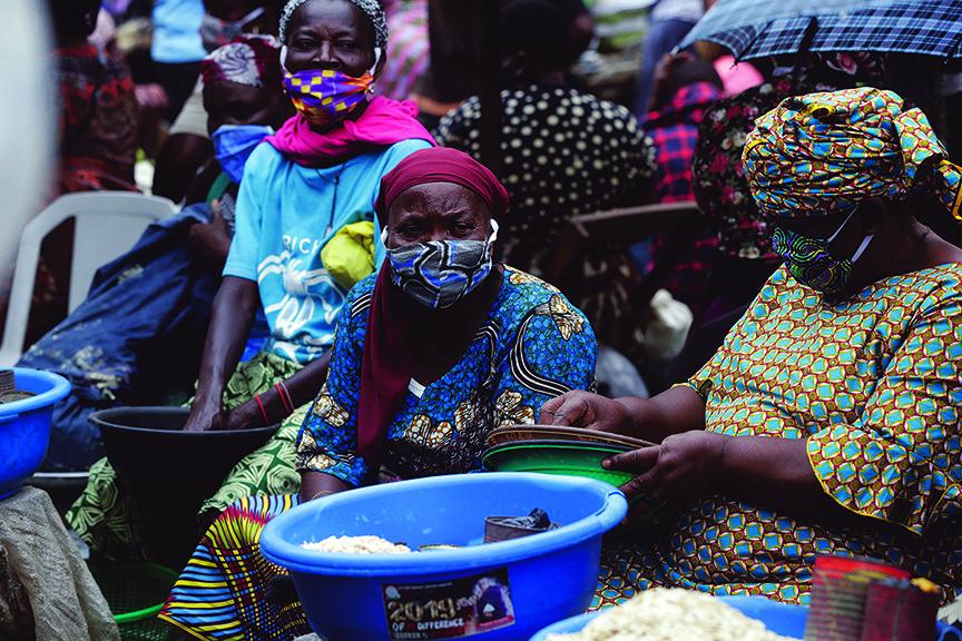 Met zelfgemaakte mondkapjes op de markt in Lagos Nigeria, waar de regels versoepeld werden en het aantal besmettingen steeg. © AP Photo/Sunday Alamba