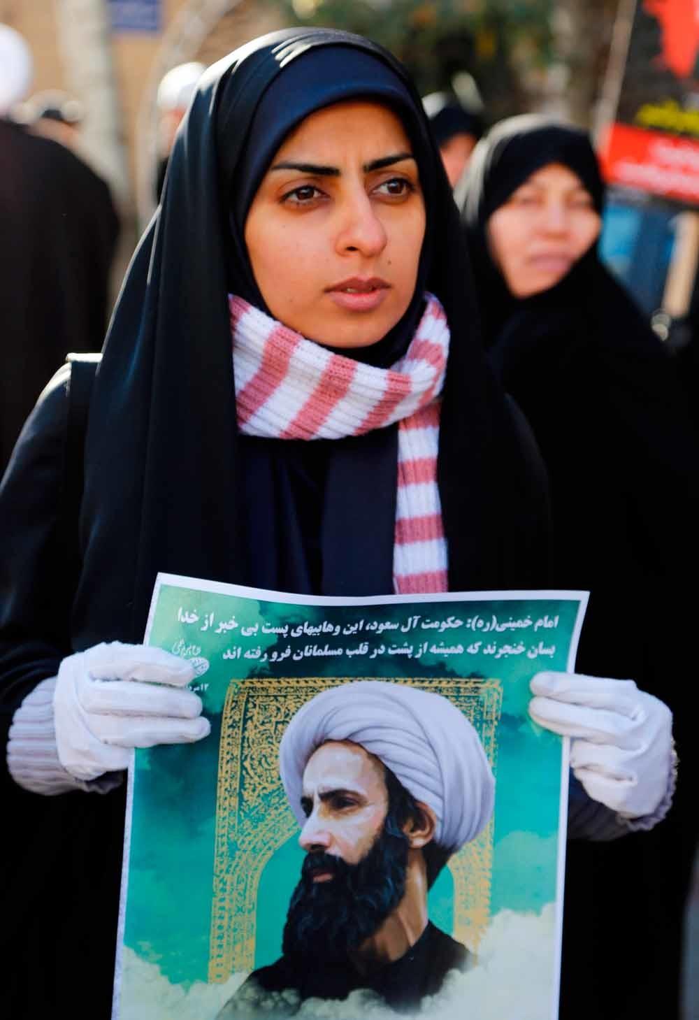 Een Iraanse vrouw houdt een poster omhoog van Nimr Baqir al-Nimr voor de Saoedische ambassade in Teheran. – © Getty