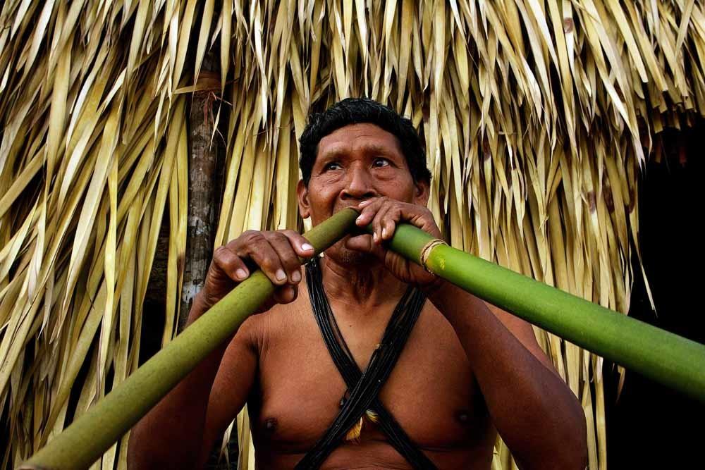 Een lid van de Cinta-Larga bespeelt een traditioneel instrument. © Lalo de Almeida / HH