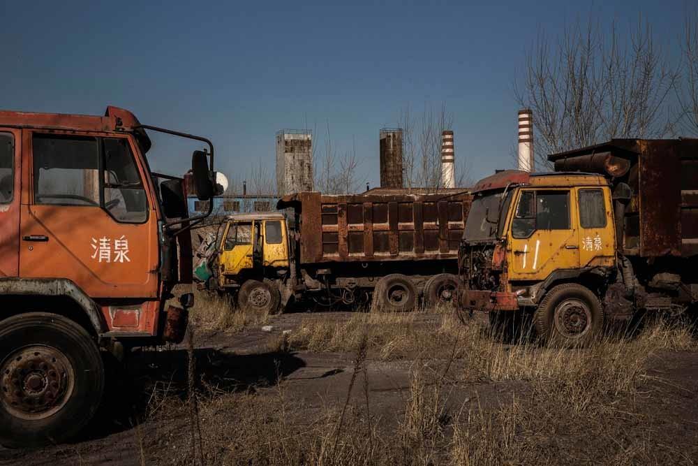 Trucks staan weg te roesten bij de verlaten staalfabriek in Qingquan. – © Kevin Frayer / Getty Images