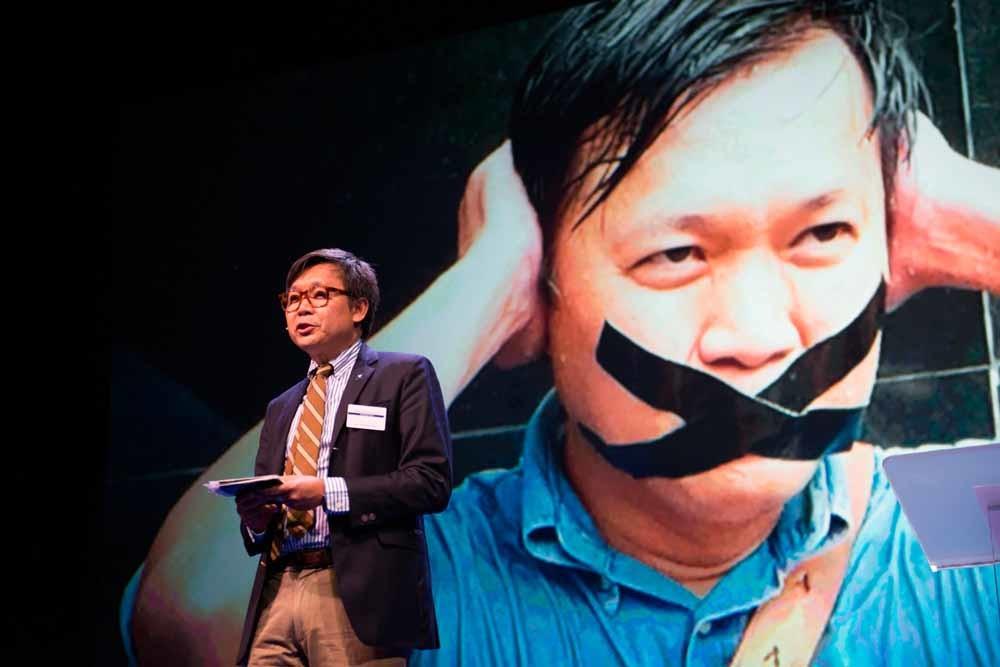 Journalist Pravit Rojanaphruk op het Oslo Freedom Forum in 2015. Op de achtergrond een foto van zijn arrestatie door de militaire junta. – © Corbis