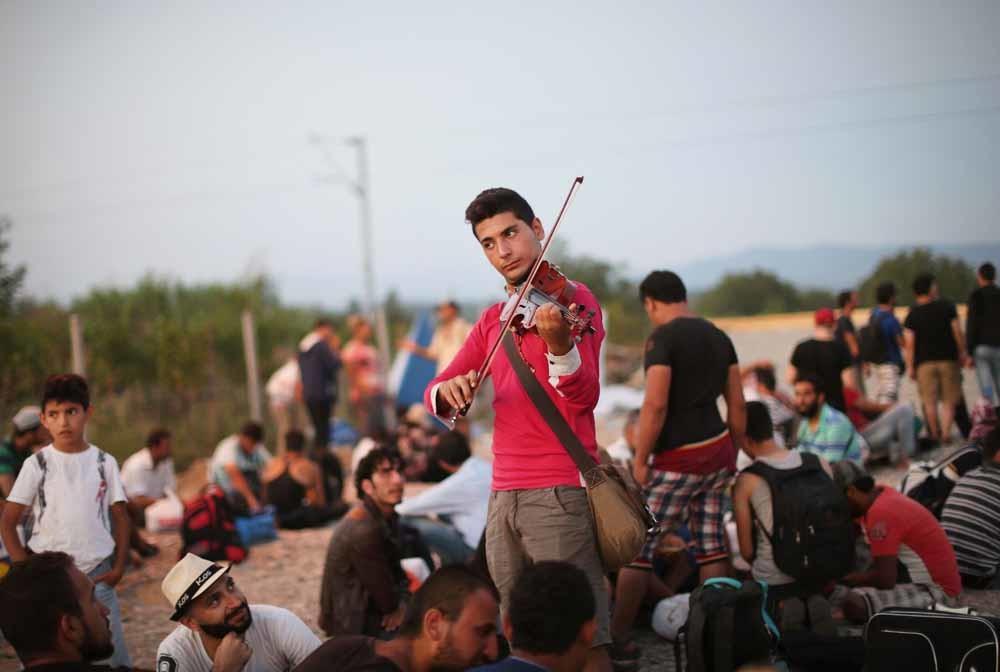 Rami Basisah speelt, zijn landgenoten kijken toe. – © Jure Erzen