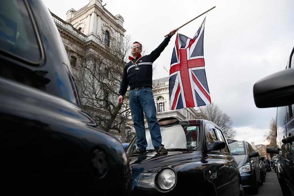 Een Londense taxichauffeur zwaait met een vlag uit protest tegen Uber. – © Reuters