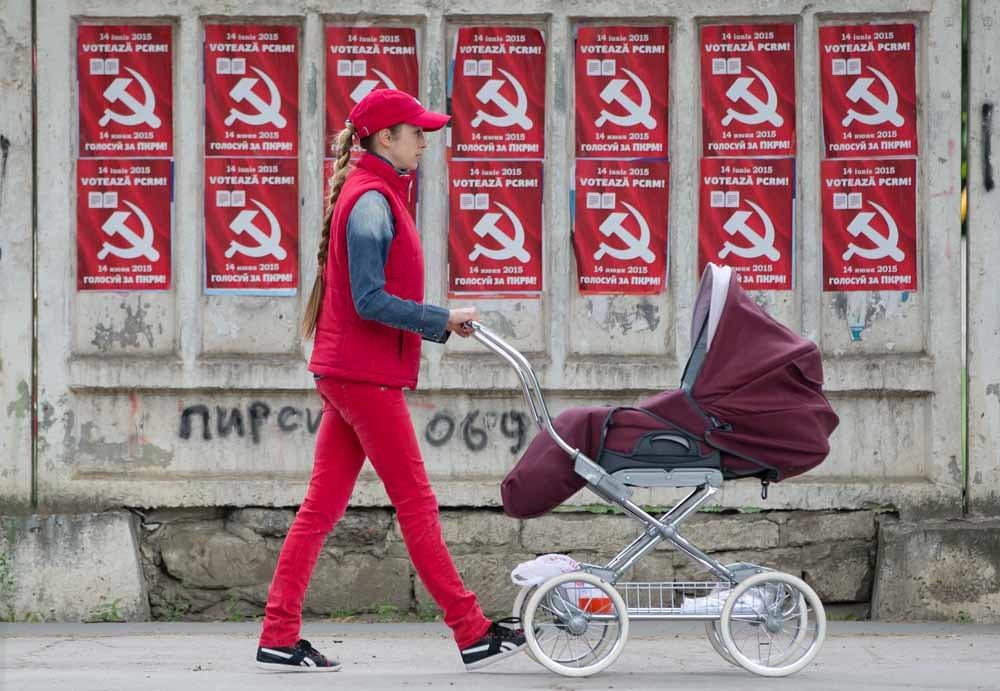 Een vrouw met kinderwagen passeert a ches van de Communistische Partij in Chisinau, Moldavië. – © Vadim Ghirda / Hollandse Hoogte