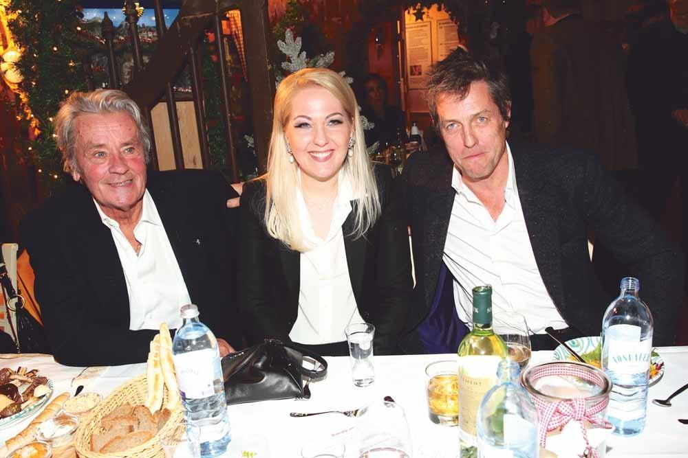Alain Delon, Kathrin Glock (echtgenote van Gaston Glock) en Hugh Grant op een feestje in Oostenrijk in 2014. – © Gisela Schober / Getty Images
