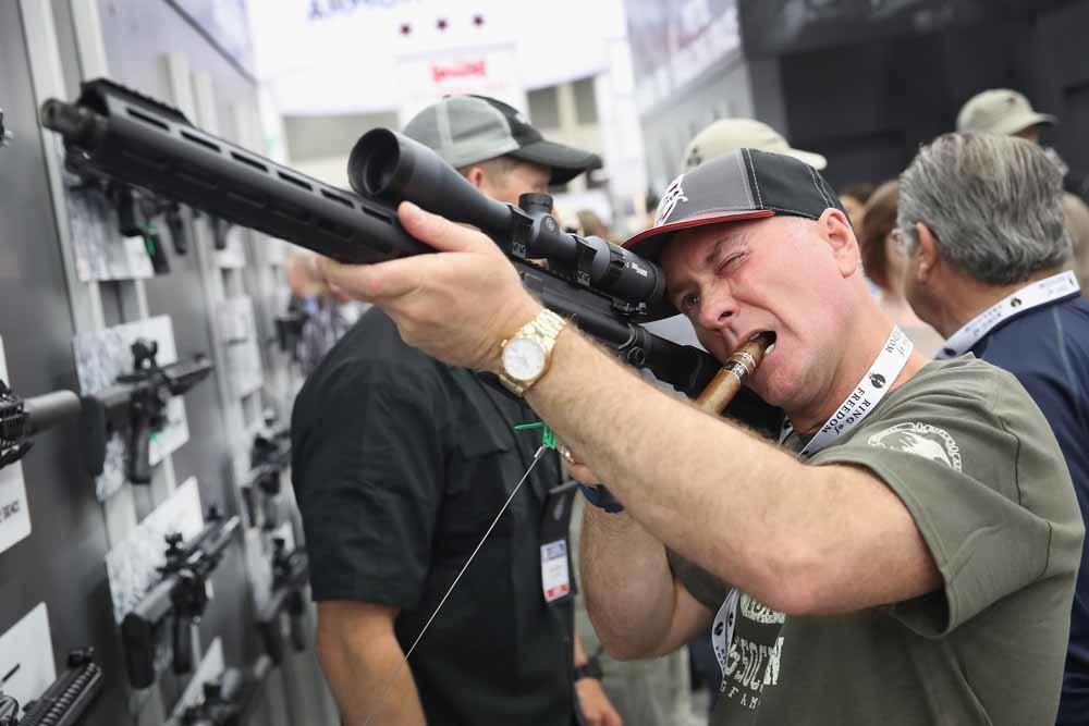 Een man test een Sig Sauer-geweer op een jaarlijkse bijeenkomst van de NRA in Louisville, Kentucky. – © Scott Olson / Getty Images
