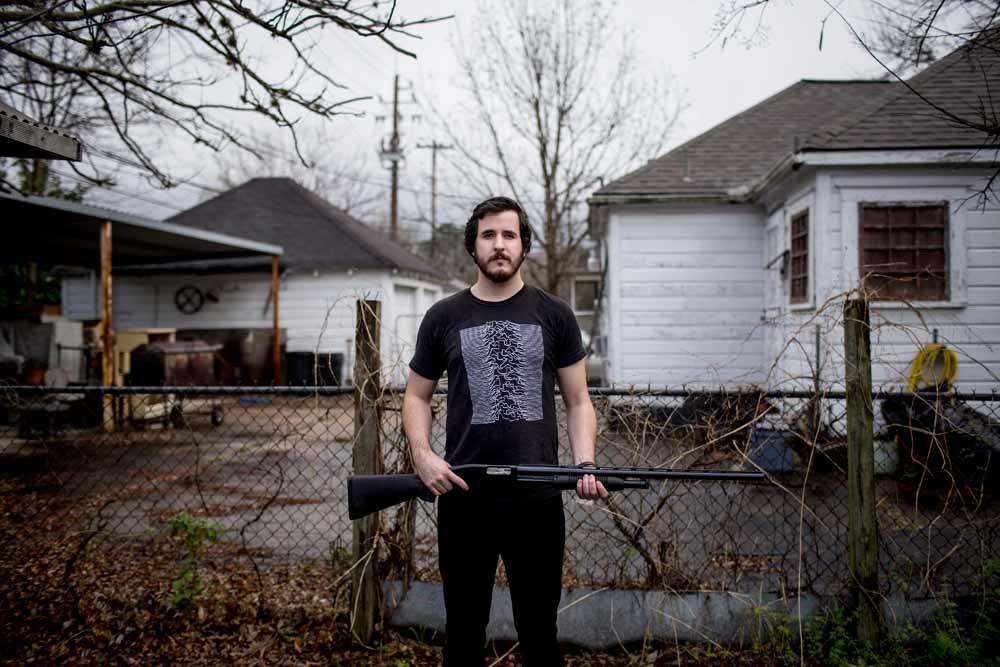 Alex, een inwoner van Houston, poseert met een Mossberg-geweer dat hij gebruikt 'om te jagen en mezelf te beschermen'. Hij en zijn broer bezitten samen vijf vuurwapens. – © HH