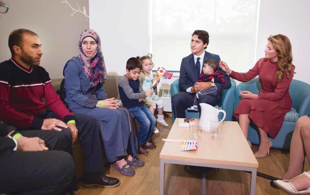 De Canadese premier Justin Trudeau en zijn vrouw met Syrische vluchtelingen in Vancouver. – © Jonathan Hayward / Reuters
