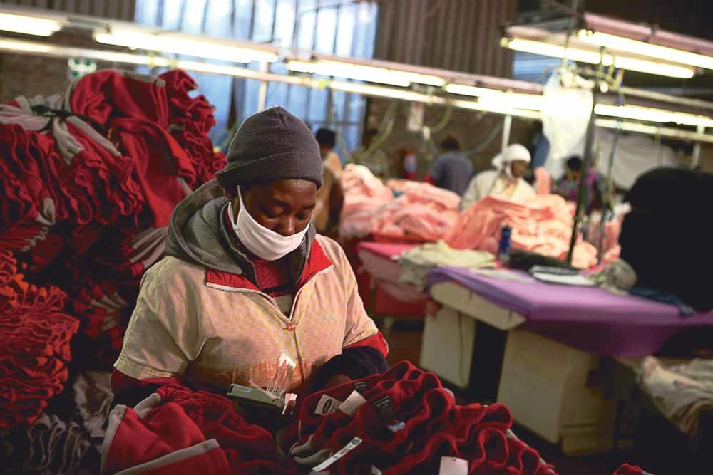 Een textielarbeidster aan het werk in een fabriek in Maseru, Lesotho. – © Pieter Bauermeister / Getty