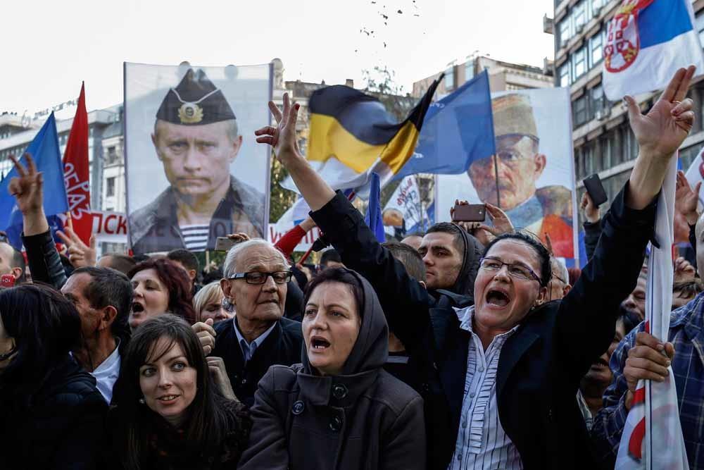 Aanhangers van de Servische nationalist Vojislav Seselj tonen hun loyaliteit aan Poetin. Seselj is overigens ook een van van Trump. – © Marko Djurica / Reuters