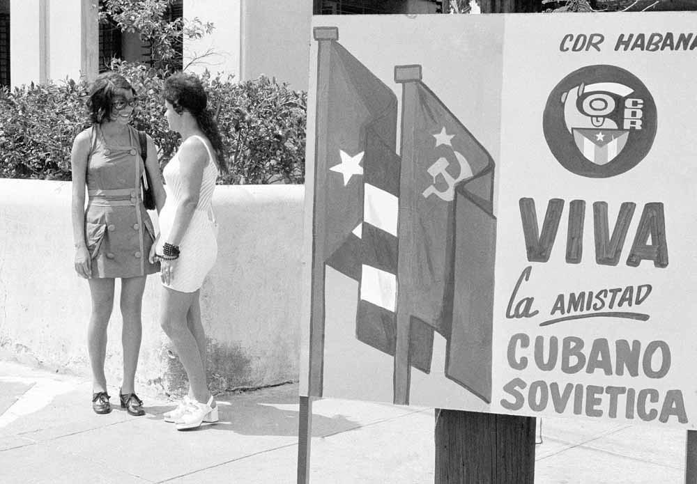 Havana, 1975. Twee vrouwen kletsen op straat. Op het bord staat: Lang leve de vriendschap tussen de Sovjet-Unie en Cuba. – © AP Photo / Charles Tasnadi