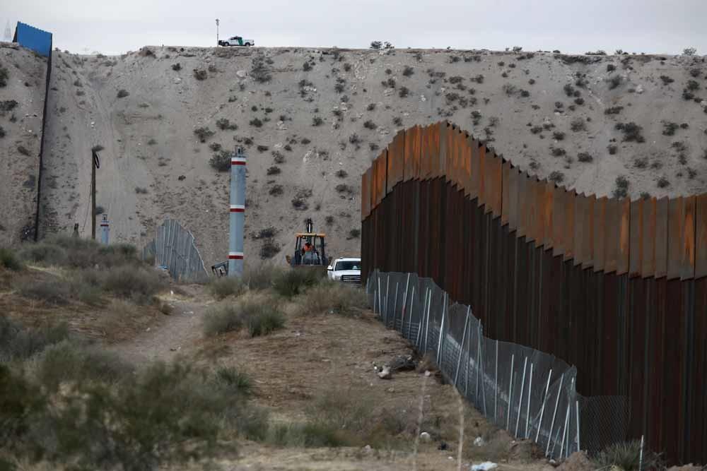 Arbeiders werken aan een hek bij de grens tussen de VS en Mexico. – © HH